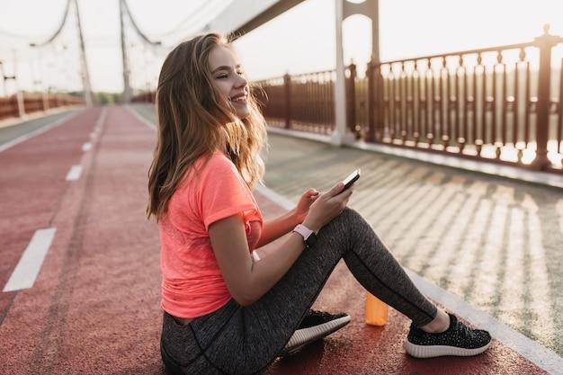 Zalig meisje in zwarte sneakers zittend op sintelbaan en lachen. emotionele jonge vrouw poseren met smartphone en een fles sap.