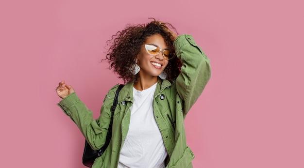 Zalig meisje met het afrikaanse kapsel lachen. het dragen van stijlvolle oorbellen, zonnebril en groene pakking. roze muur.