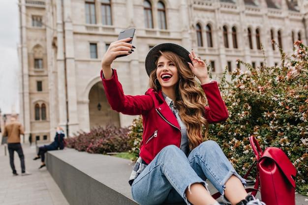 Zalig wit vrouwelijk model in retro jeans die selfie met glimlach maakt