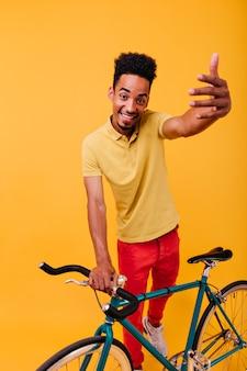 Zalige afrikaanse man poseren met groene fiets. binnen schot van emotioneel donkerbruin mannelijk model dat zich met fiets bevindt.