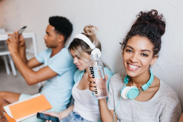 Zalige afrikaanse meisje fles water houden en poseren met een glimlach met vrienden. portret van krullende vrouwelijke student, blonde jonge vrouw en zwarte kerel die foto maken.