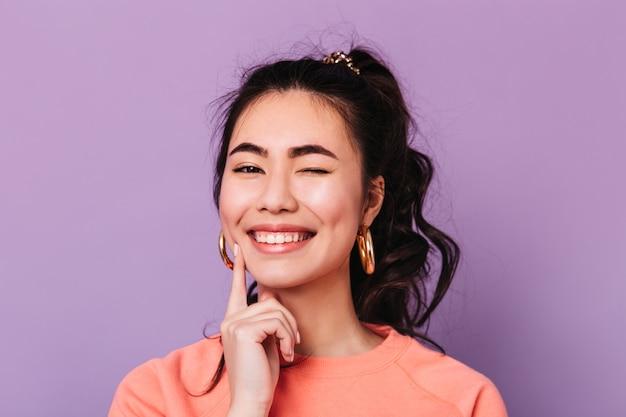 Zalige aziatische vrouw die met krullend haar grappige gezichten maakt. studio shot van blije koreaanse jonge vrouw.