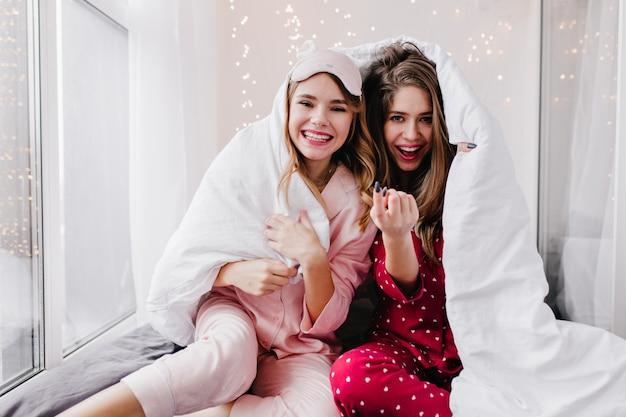 Zalige blanke meisjes die in weekendochtend positieve emoties uiten. gelukkig europese vrouwelijke modellen in nachtkostuums zitten in een gezellige kamer.