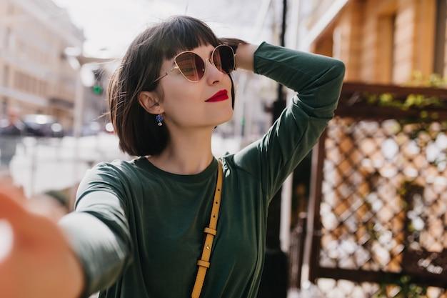 Zalige blanke vrouw met kort haar selfie maken in goede lentedag. buitenfoto van geïnteresseerd meisje in een stijlvolle zonnebril en groene trui.