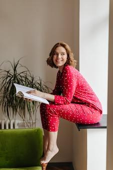 Zalige blootsvoets vrouw lezing tijdschrift. binnen schot van lachende vrouw in pyjama zittend op de vensterbank.