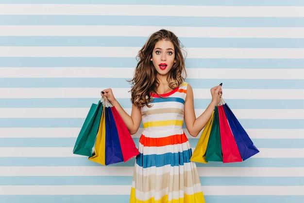 Zalige donkerharige vrouw die zomerkleren koopt. indoor foto van vrij europees meisje poseren na het winkelen.