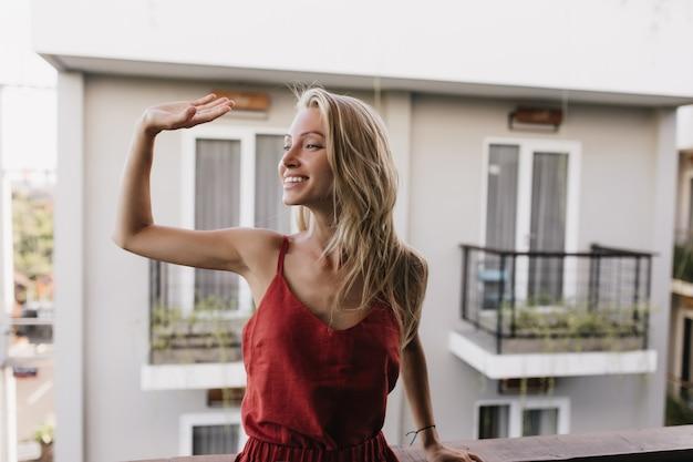 Zalige gelooide vrouw in pyjama zwaaiende hand met glimlach. verbazend kaukasisch vrouwelijk model dat zich bij balkon bevindt.