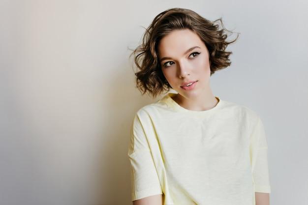 Zalige jonge vrouw met donkere ogen wegkijken terwijl poseren op lichte muur. binnenfoto van elegant bleek kaukasisch meisje met krullend kapsel.