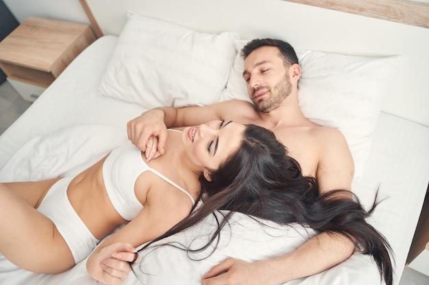 Zalige jonge vrouw met los lang haar dat op de borst van haar echtgenoot in een slaapkamer rust