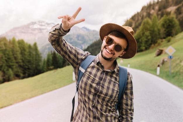 Zalige jongeman in trendy zonnebril poseren met glimlach tijdens wandeltocht naar italiaanse alpen vredesteken tonen