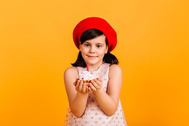 Zalige jongen viert verjaardag. vooraanzicht van preteen meisje met cake geïsoleerd op gele muur.