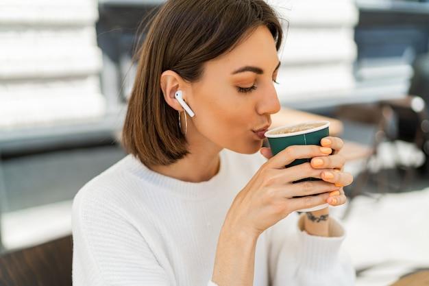 Zalige kortharige vrouw die geniet van cappucino in café, een gezellige witte trui draagt en naar favoriete muziek luistert via oortelefoons