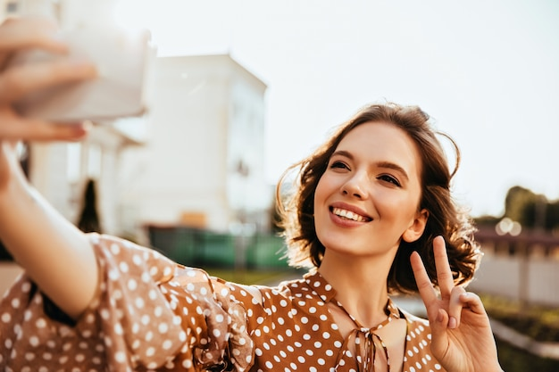 Zalige kortharige vrouw in bruine kleding die geluk uitdrukt. vrolijke dame die telefoon vasthoudt en selfie maakt.