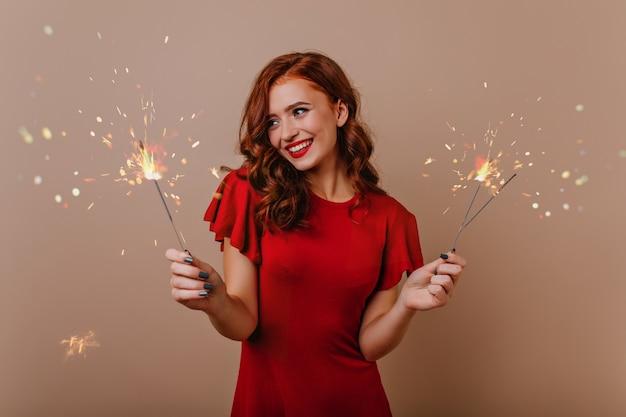 Zalige krullende vrouw met sterretjes die van kerstmistijd genieten. indoor foto van lachen mooi meisje met bengalen lichten.