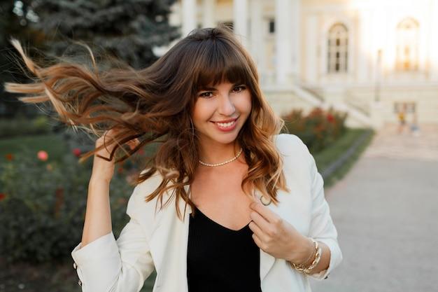 Zalige lachende vrouw spelen met haren en genieten van uotumn dag in europese stad. elegante uitstraling.