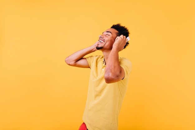 Zalige man met mooie glimlach luisteren muziek. binnen schot van afrikaans mannelijk model in hoofdtelefoons die positieve emoties uitdrukken.