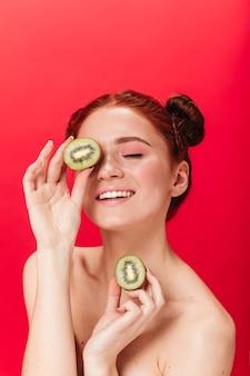 Zalige meisjesholding gesneden kiwi. studio shot van charmante gember vrouw geïsoleerd op rode achtergrond met fruit.