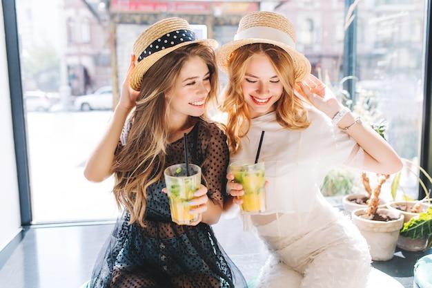 Zalige mooie dames in modieuze jurken zitten in de buurt van groot raam met glazen ijskoude cocktails en lachen