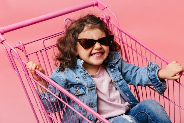 Zalige preschool kind zit in winkelwagen. lachend kind in spijkerbroek met plezier op roze achtergrond.