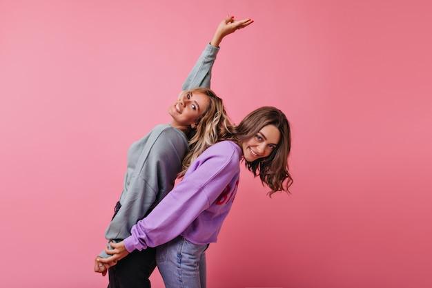 Zalige vriendinnen in straatkleren hand in hand op roze. positieve blanke dames dansen met plezier.
