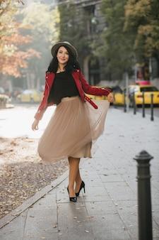 Zalige vrouw in hoge hakken spelen met haar lange rok terwijl poseren in park