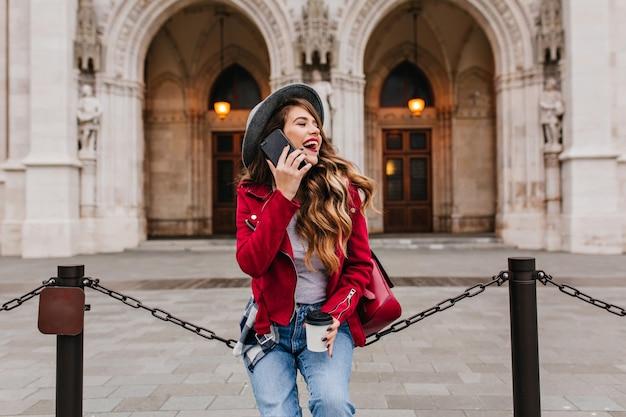Zalige vrouw met glanzend krullend haar wegkijken met glimlach tijdens telefoongesprek