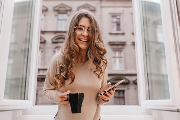 Zalige vrouw met telefoon en lachen tijdens fotoshoot thuis