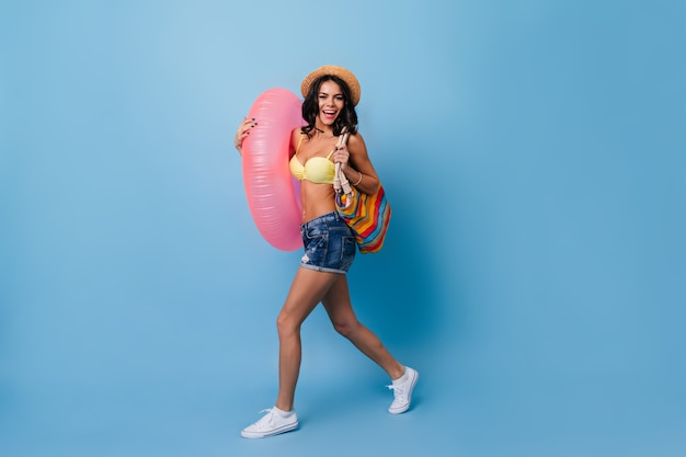 Zalige vrouw met zwemmende cirkel die op blauwe achtergrond danst