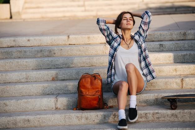 Zalige vrouw zittend op de trap genietend van zacht zonlicht met gesloten ogen