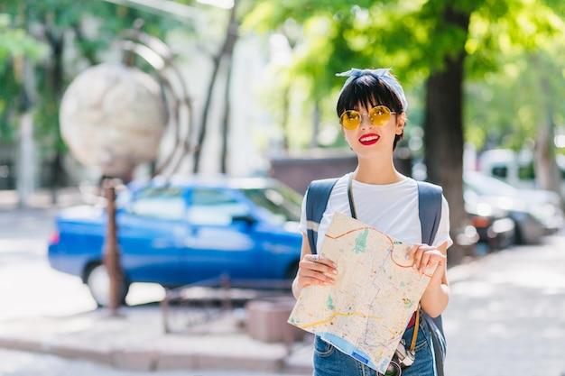 Zalige vrouwelijke reiziger met kort zwart haar die nieuwe landen verkent, stadsplattegrond vasthoudt en glimlacht