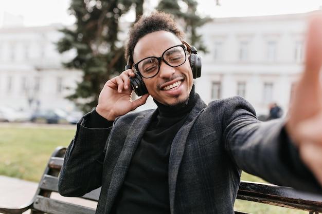 Zalige zwartharige afrikaanse man selfie maken op stad. buiten foto van gelukkig lachen mulat man met krullend kapsel.