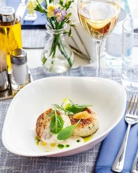 Zalm en kabeljauw viskoteletten met spinazie en snoekkaviaar met witte saus in een restaurant serveren. keto, paleo, fodmap dieetvoeding. detailopname.
