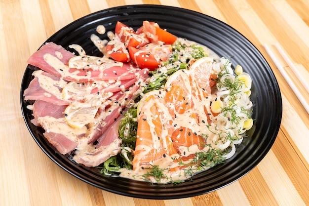 Zalm en tonijn sashimi in een salade met kruiden. voor elk doel.