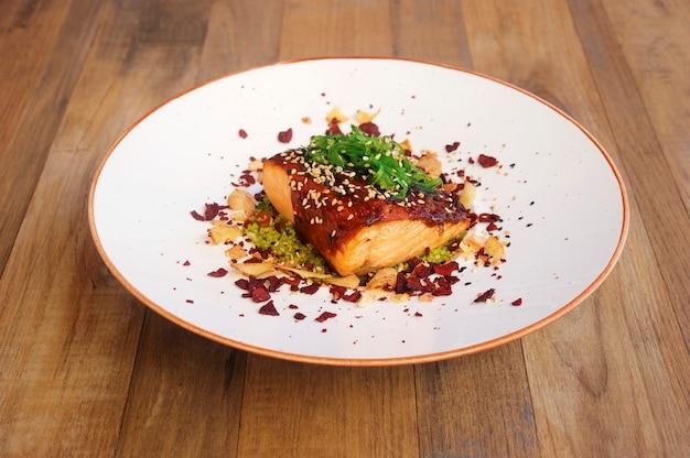 Zalm gekookt met saus en sesam op houten achtergrond.