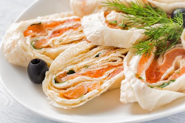 Zalm lavash broodjes met dille, kaas en zwarte olijven op witte plaat