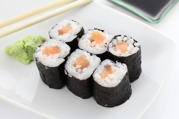 Zalm maki sushi met stokjes en sojasaus in wit