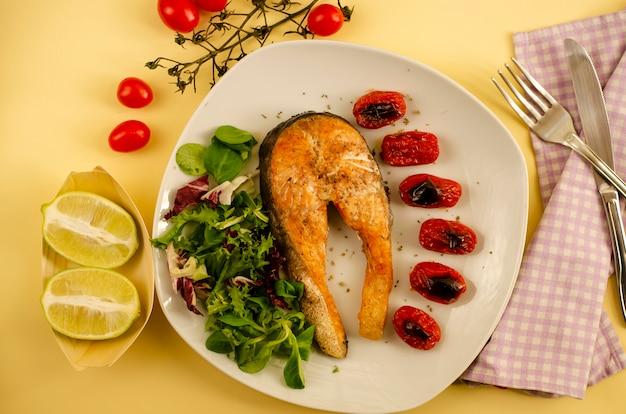 Zalm met geroosterde kerstomaten en gemengde slablaadjes en helften van citroen. mediterraans eten. bovenaanzicht