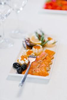 Zalm met voorgerechten op een witte plaat en een vork op de tafel