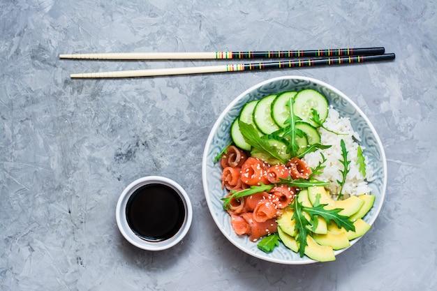 Zalm por met avocado, rucola en komkommer in een kom, balsamico saus en eetstokjes.