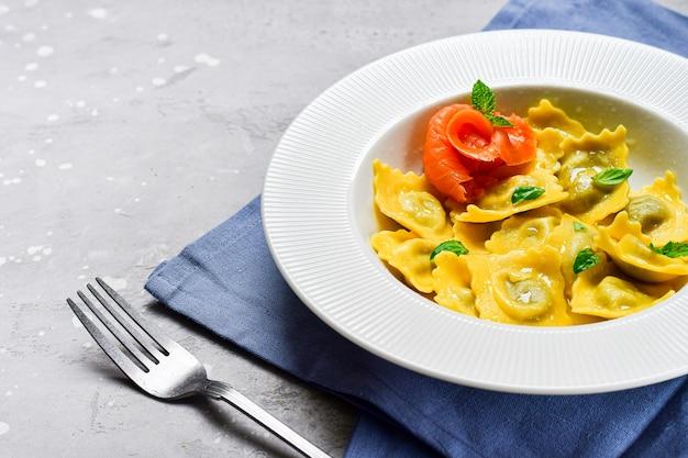 Zalm ravioli traditionele italiaanse gerechten met verse basilicum in een witte plaat op een grijze stenen tafel. recept italiaans eten. plat eten