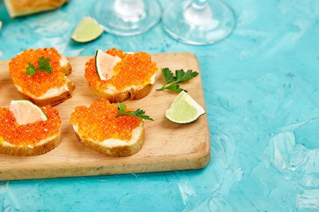 Zalm rode kaviaar in kom en sandwiches met op houten snijplank