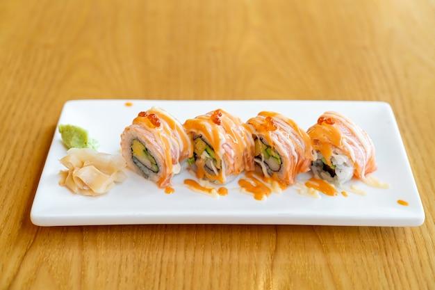 Zalm roll sushi met saus bovenop - japans eten stijl