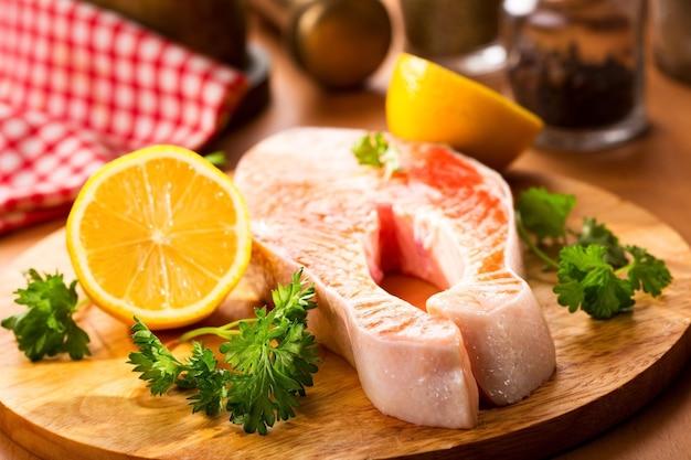 Zalm steak met citroen en peterselie op een houten bord