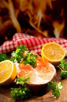 Zalm steak met citroen en peterselie op houten tafel