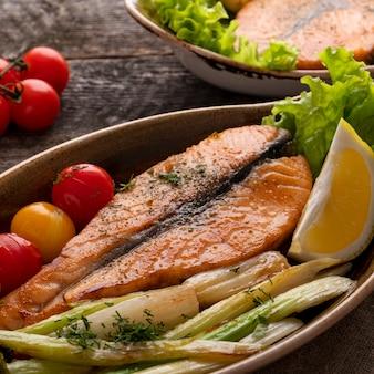 Zalm steak met gebakken tomaten en selderij. vis met groenten.