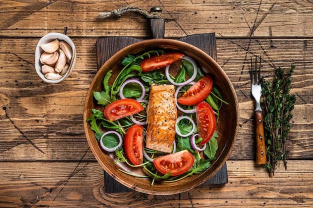 Zalm steak salade met groene bladeren rucola, avocado en tomaat in een houten plaat. houten achtergrond. bovenaanzicht.
