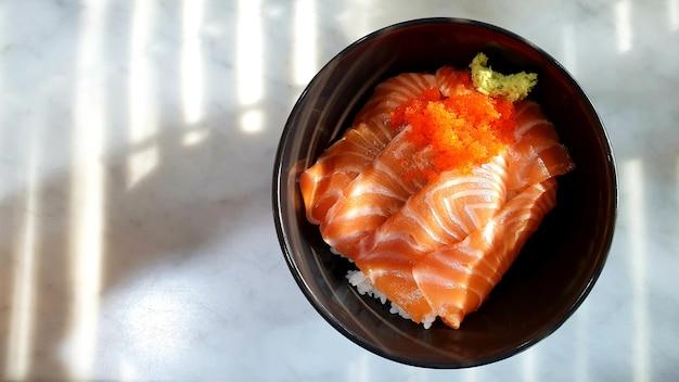 Zalm sushi rijst ja panese eten in een kom op de tafel en kopieer de ruimte
