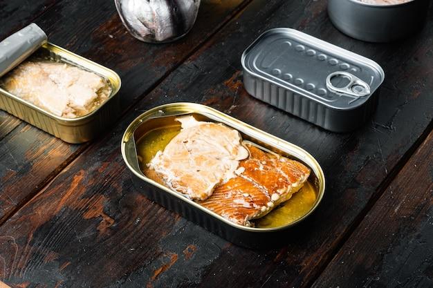 Zalm, tonijn, forelmakreel en ansjovis - ingeblikte vis in blikjes, op oude donkere houten tafel