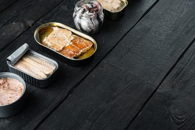 Zalm, tonijn, forelmakreel en ansjovis - ingeblikte vis in blikjes set, op zwarte houten tafel