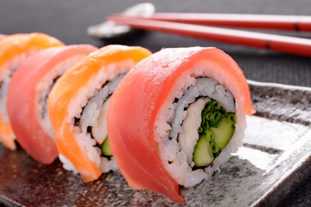 Zalm tonijn sushi roll met chopsticks close-up